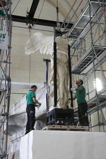 Unos operarios elevan la estatua de la Victoria de Samotracia en el proceso de colación en su lugar en el Museo del Louvre.