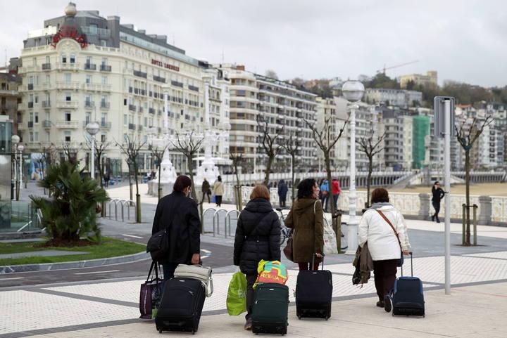 Unos turistas caminan por el paseo de la Concha en San Sebastián
