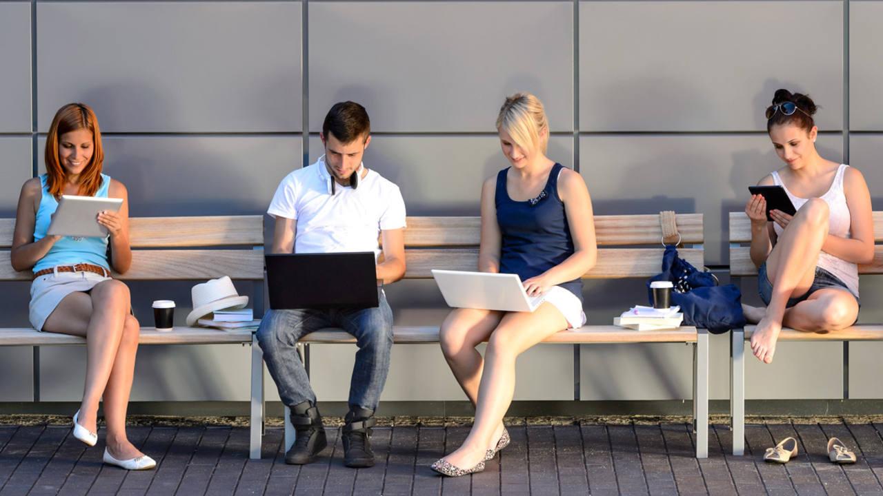 Unos universitarios consultan sus ordenadores en un campus