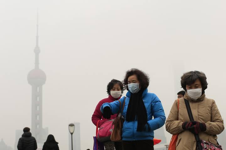Varias mujeres con mascarilla, delante de la Torre de la Televisión de Shanghai
