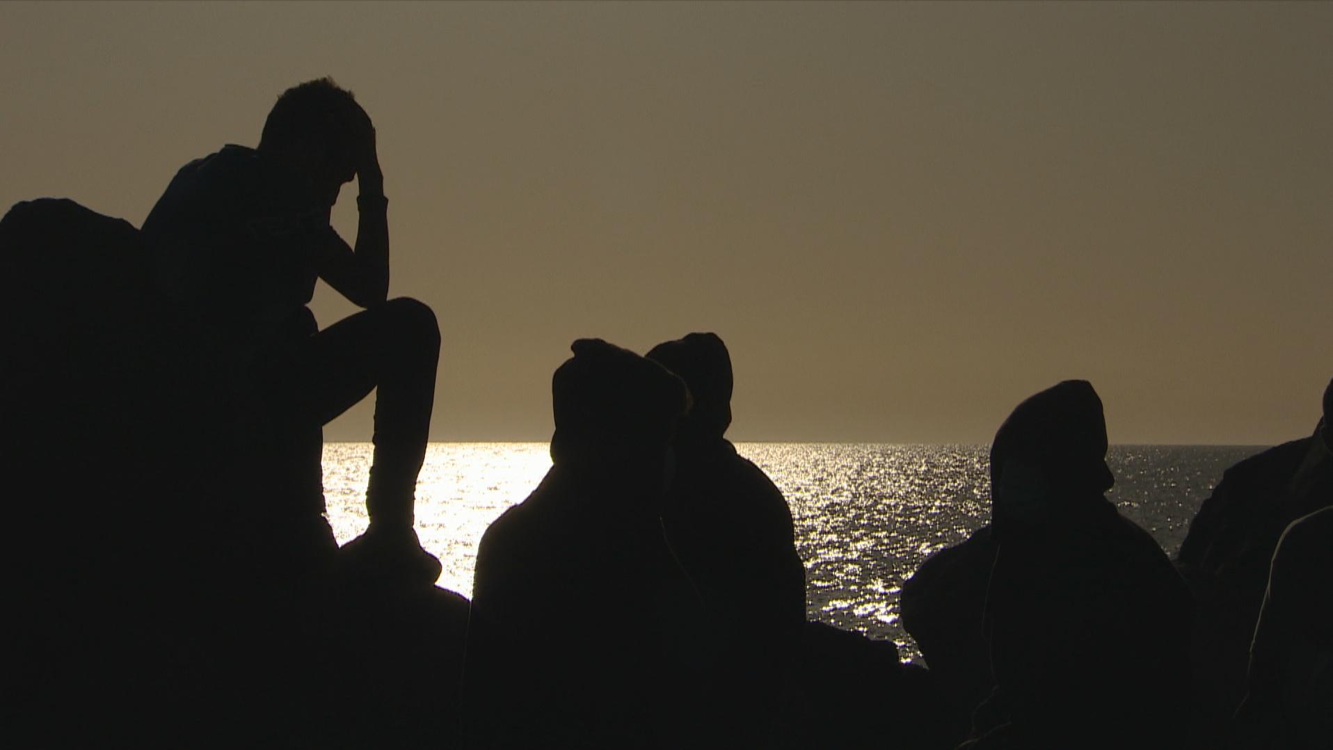 Varios migrantes esperan en el muelle de Arguineguín