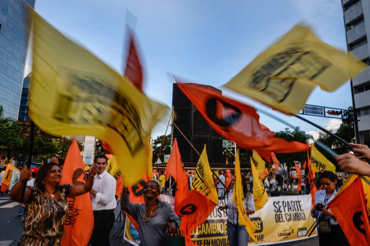 Varios opositores enarbolan banderas en el mitin de final de campaña de la Mesa de la Unidad Democrática en Caracas
