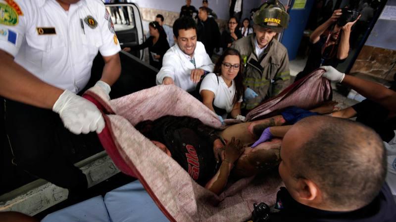 Varios voluntarios colaboran para trasladar a una de las heridas en el incendio del centro de menores de San José Pinula