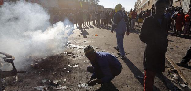Vecinos partidarios de la expulsión de extranjeros observan un coche incendiado en un nuevo ataque xenófobo registrado en el centro de Johannesburgo (Sudáfrica), el pasado viernes 17 de abril.