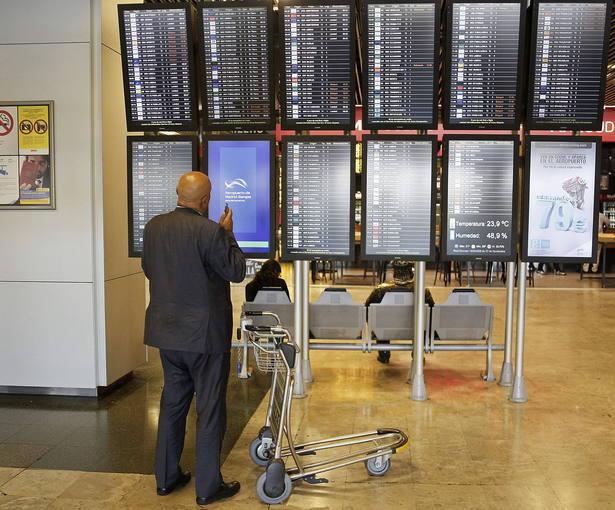 Un viajero consulta los horarios de los vuelos en paneles informativos del aeropuerto de Barajas