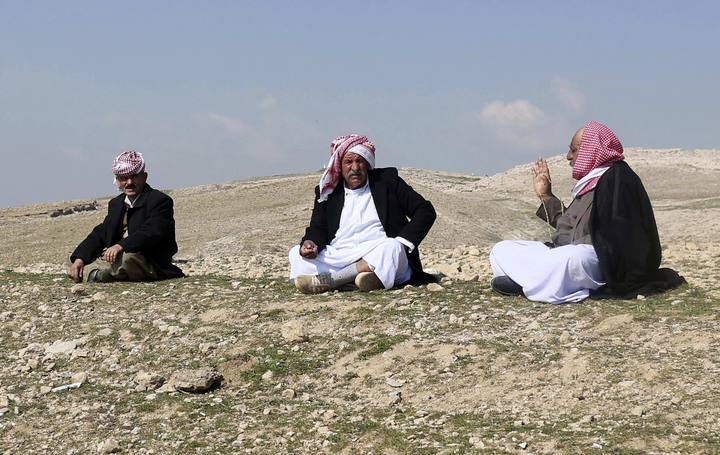 Yazidi refugees talk on a hill overlooking their refugee camp on the outskirts of Duhok