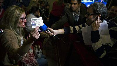 Una agraciada con el número 00000 celebra el premio en el salón de loterías