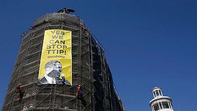 Seis activistas de Greenpeace protestan colgando un cartel contra el TTIP durante la visita de Obama