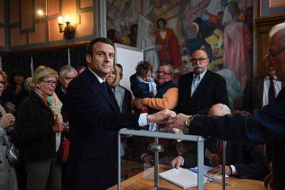 El candidato presidencial Emmanuel Macron (C) vota en Le Touquet, al norte de Francia