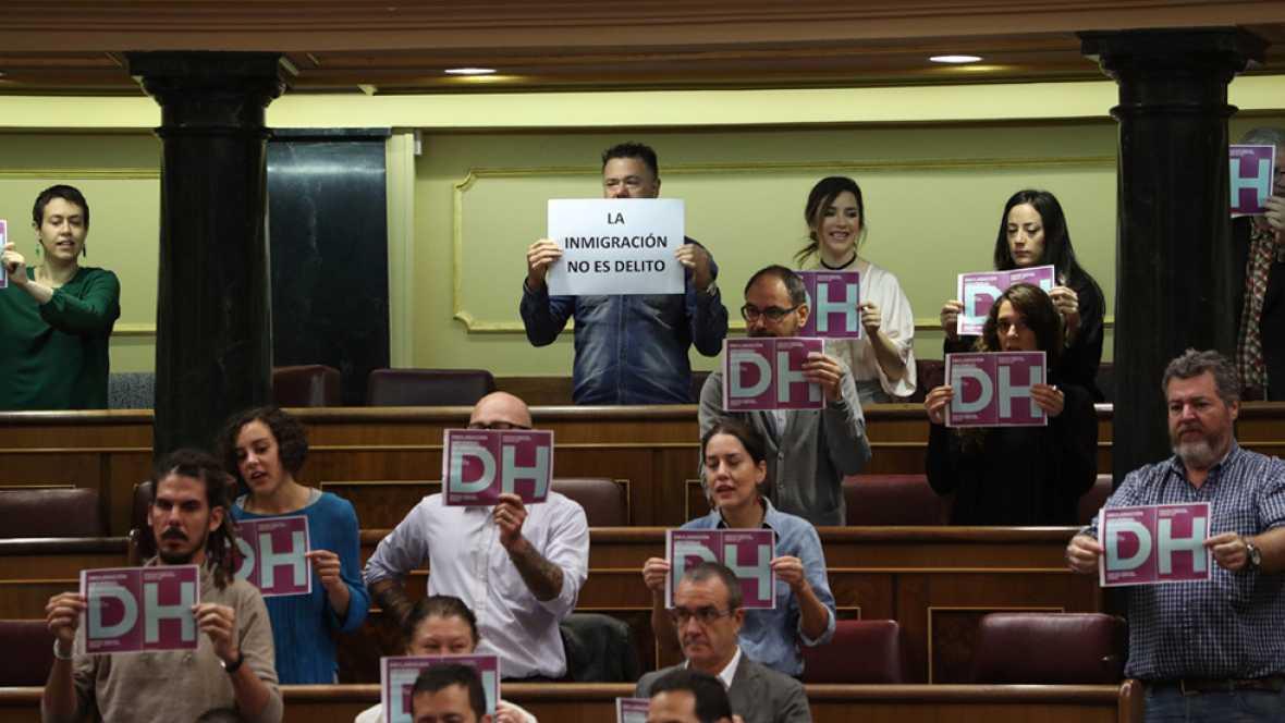 Decenas de diputados de Unidos Podemos han protagonizado una protesta al inicio del pleno del Congreso exhibiendo carteles con las iniciales DH, de Derechos Humanos, que han depositado después en el escaño del ministro del Interior, Jorge Fernández D